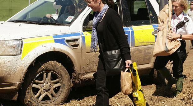 Police officers carry evidence bags into the hospitality area following the death of Christopher Shale at the Glastonbury Festival