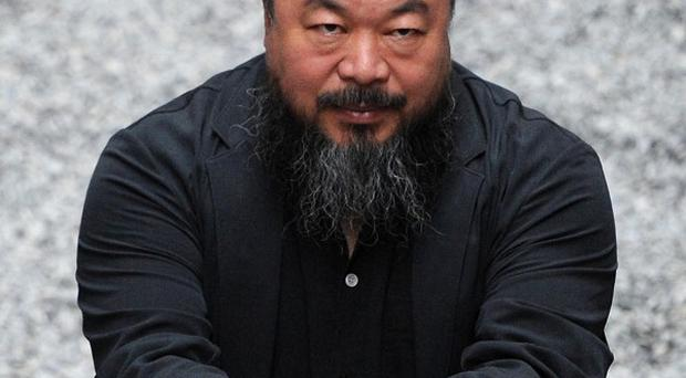 Chinese artist Ai Weiwei with his work 'Sunflower Seeds' at the Tate Modern