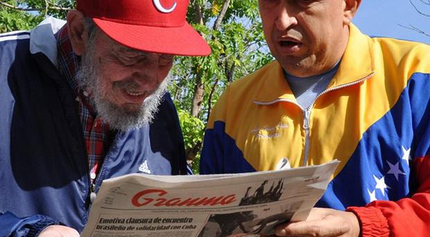 Fidel Castro and Hugo Chavez look at Granma state newspaper in Havana, Cuba (AP)