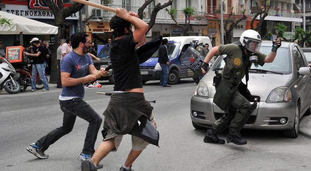 A riot policeman runs from angry protesters in the northern Greek port city of Thessaloniki, Wednesday, May 5, 2010.