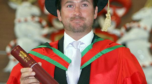Former US Open golf champion Graeme McDowell holds his honorary doctorate of science degree at the University of Ulster