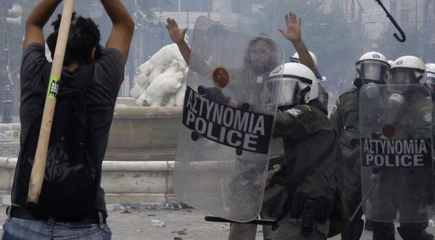A protester prepares to hit riot police with a stick during clashes at Syntagma square, central Athens (AP)
