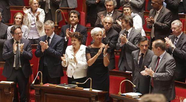 Members of the French National Assembly applaud after two French journalists held hostage in Afghanistan are freed (AP)