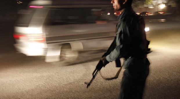 An Afghan police officer stands guard stops vehicles entering the road leading to Inter Continental hotel in Kabul, Afghanistan (AP)