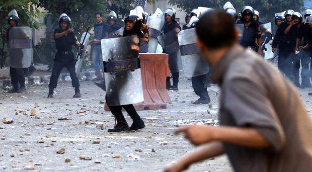 Riot police and demonstrators clash near the interior ministry in Cairo (AP)