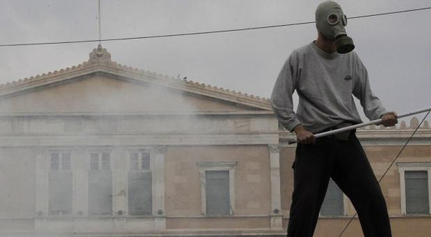 A protester holds an iron stick as he stands in front of the Greek parliament during clashes at Athens's main Syntagma square (AP)
