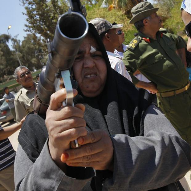 A Libyan woman holds a rocket propelled grenade launcher at a weapons training session in Libya (AP)
