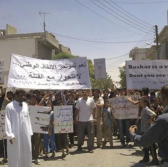Protesters hold up banners during a demonstration against the Syrian regime (AP Photo/Shaam News Network)