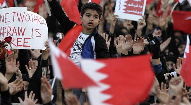 Bahraini anti-government protesters chant slogans at the Pearl roundabout in Manama, Bahrain (AP)