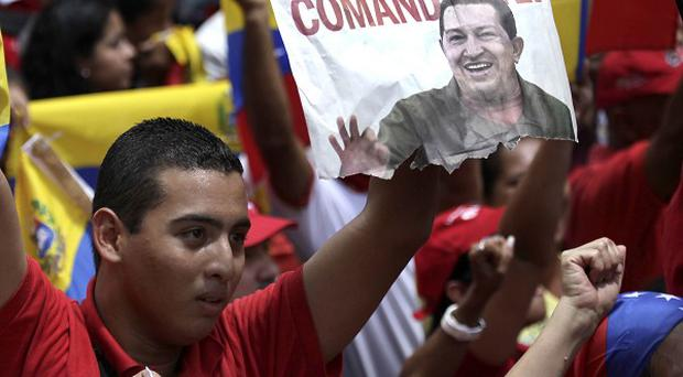 Supporter of Venezuela's president Hugo Chavez hold up an image of him during a march in Caracas, Venezuela (AP)