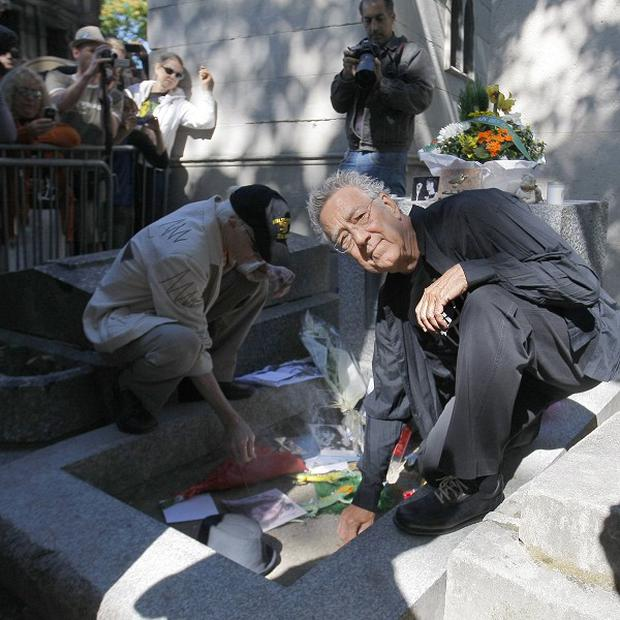 Ray Manzarek and Robby Krieger light candles at the grave of Jim Morrison