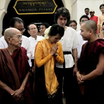Aung San Suu Kyi pays respect to a Buddhist monk during her visit to a pagoda along with her youngest son Kim Aris in Bagan (AP)