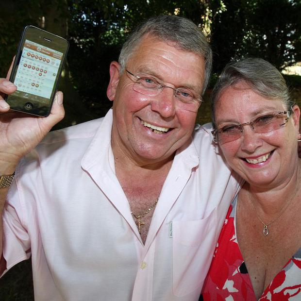 Chris Bowers and wife Sue along with the iPhone which gave them news of the multimillion-pound win
