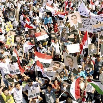 In a photo released by the Syrian official news agency SANA, Syrian supporters of President Bashar Assad demonstrate their approval(AP)