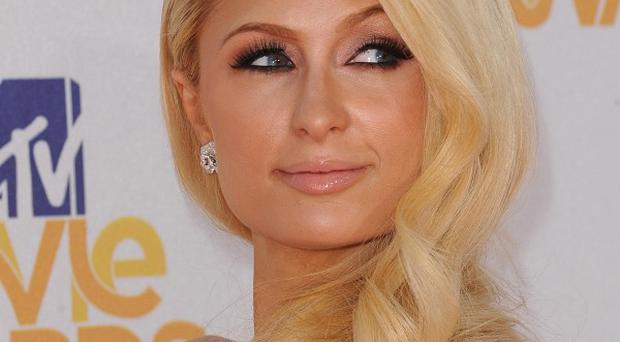 A man has been charged with f violating a restraining order that bars him from being within 200 yards of Paris Hilton or her home