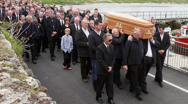 The coffin of Johnny Curry is carried past Rathlin Island harbour where more than 1,000 mourners attended his funeral