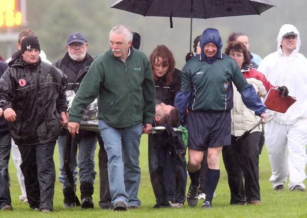 Referee Simon Brady is stretchered away after suffering concussion following the ladies Tyrone county final between Carrickmore and Augher