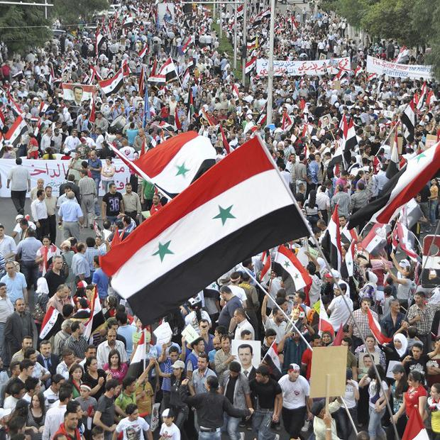 Pro-Syrian president Bashar Assad protesters wave flags in support of their leader (AP/SANA)