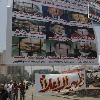 Egyptian protesters walk under a banner featuring pictures of government officials during protests in Tahrir Square, Cairo