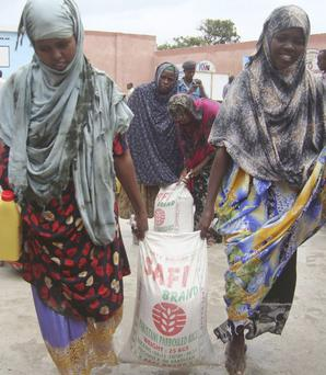 Women from southern Somali carry food after receiving aid from a Muslim Aid Organization in Mogadishu, Somalia, after fleeing from southern Somalia, Sunday, July 10, 2011.