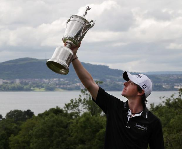 US Open winning golfer Rory McIlroy poses with his trophy on a green at Holywood Golf Club