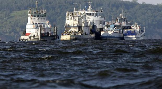 Rescue boats try to locate passengers of a tourist boat that sunk on the Volga (AP)