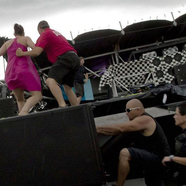 Police, security and Bluesfest personnel rush onto the wreckage of the main stage at the Ottawa Bluesfest (AP)