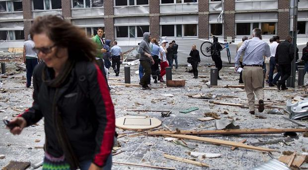 A woman walks through debris after the explosion in Oslo (Scanpix)