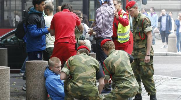 Wounded people are treated in the street in the centre of Oslo, Friday July 22, 2010, following an explosion that tore open several buildings including the prime minister's office, shattering windows and covering the street with documents and debris