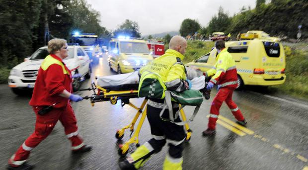 Medics and emergency workers escort an injured person from a camp site on the island of Utoya, Norway Saturday July 23, 2011. A Norwegian dressed as a police officer gunned down at least 84 people at an island retreat, police said Saturday. Investigators are still searching the surrounding waters, where people fled the attack, which followed an explosion in nearby Oslo that killed seven