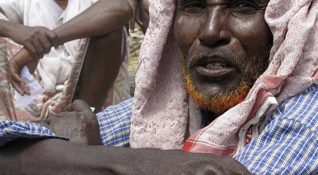 An elderly Somali man displaced by famine waits to receive food aid in the makeshift shelters in Mogadishu, Somalia (AP)