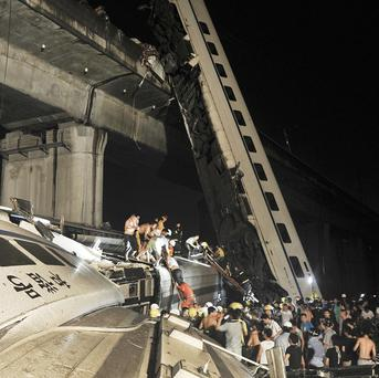 Emergency workers help passengers from the wreckage of train after two carriages from a high-speed train derailed in China (AP)