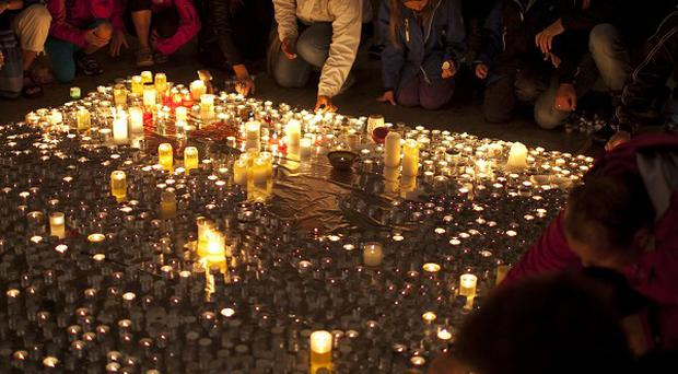People at Oslo Cathedral light candles in memory of victims of the attacks on Norway's government headquarters and an island youth retreat (AP)