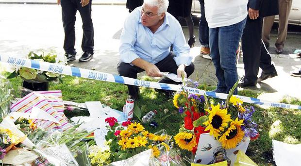 Mitch and Janis Winehouse view the flowers left by well-wishers outside the north London home of their daughter Amy