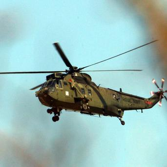 A military helicopter has helped rescue a driver who was trapped in her car after it plunged over a cliff