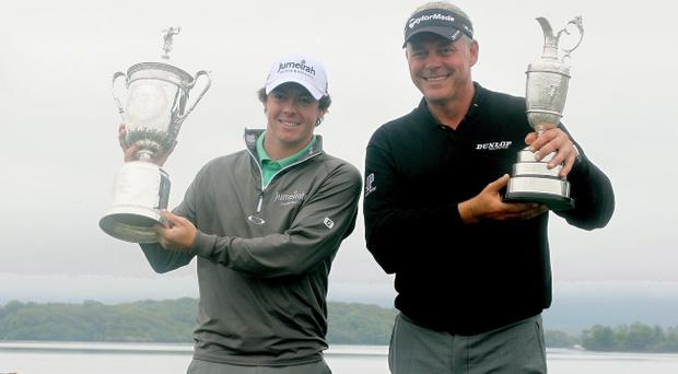 Rory McIlroy and Darren Clarke show off the US Open and Open trophies yesterday
