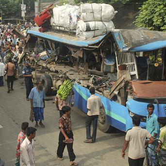 Bangladeshi villagers walk past the wreckage of a bus after it collided with a truck at Shajahanpur in Bogra district (AP)