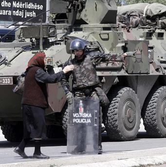 A Kosovo Serb woman asks for direction from Slovenian troops serving in the NATO-led peacekeeping mission in Kosovo (AP)