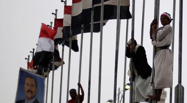 Supporters of president Ali Abduallah Saleh stand on flag poles during a rally to show support for him in Sanaa, Yemen (AP)