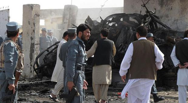Afghan police officers gather near a wrecked vehicle at the entrance of the police headquarters in Lashkar Gah (AP)