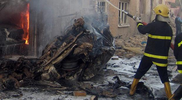 Iraqi firefighters extinguish flames after a car bomb attack in front of a Christian church in Kirkuk, Iraq (AP)