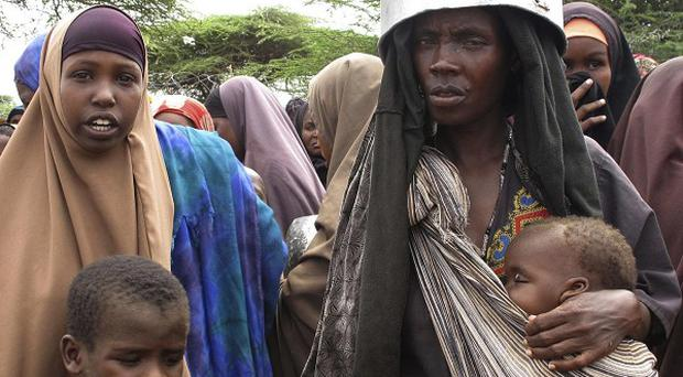 Women displaced by the drought in southern Somalia wait to receive food in one of the camps in Mogadishu (AP)