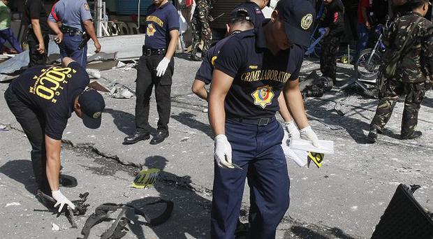 Criminal investigators gather evidence at the scene of a bomb blast in Cotabato city in the southern Philippines (AP)