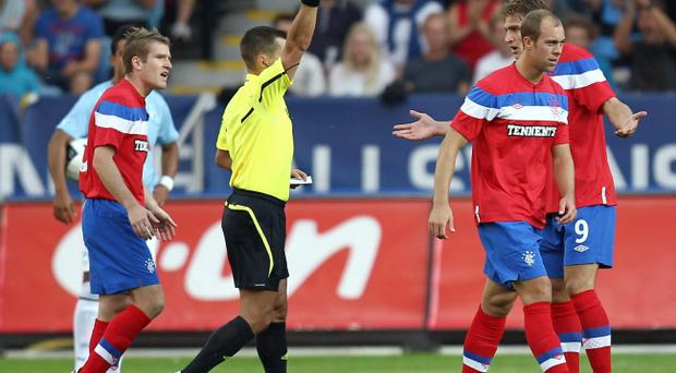 Steven Whittaker is sent off by referee Vladisav Bezborodov as Rangers were put out of the Champions' League by Malmo on goal difference