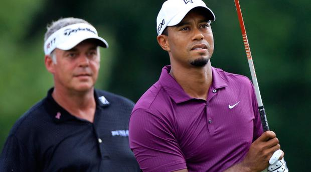 AKRON, OH - AUGUST 04: Tiger Woods (R) watches his tee shot alongside Darren Clarke of Northern Ireland (L) on the eighth tee during the first round of the World Golf Championships-Bridgestone Invitational on the South Course at Firestone Country Club on August 4, 2011 in Akron, Ohio. (Photo by Sam Greenwood/Getty Images)