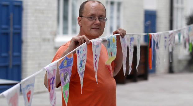 Artist Raymond Watson with some of the peaceline flags