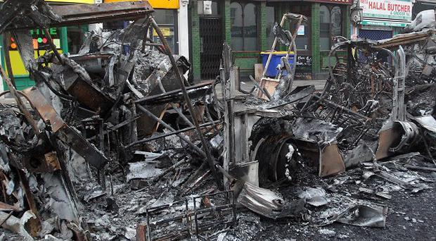 The remains of a burned out bus in Tottenham following a night of rioting