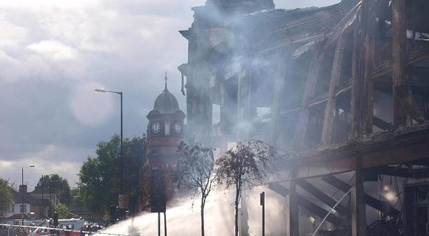 A fire hose continues to pump water onto a smouldering building in Tottenham, north London after trouble flare on Saturday night