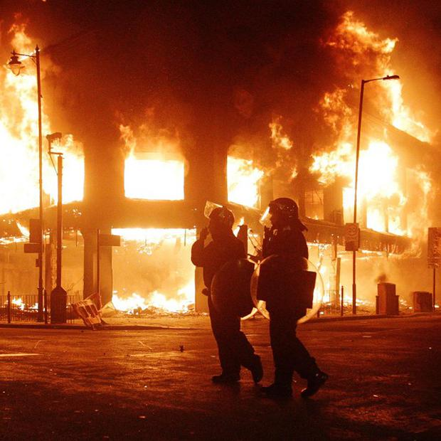 Riot police look on as fire rages through a building in Tottenham