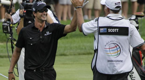 Adam Scott, left, from Australia, celebrates with caddie Steve Williams after hitting his approach to the 18th green during the final round of the Bridgestone Invitational golf tournament at Firestone Country Club in Akron, Ohio, Sunday, Aug. 7, 2011. Scott went on to make birdie and win by four shots at 17 under par. (AP Photo/Amy Sancetta)